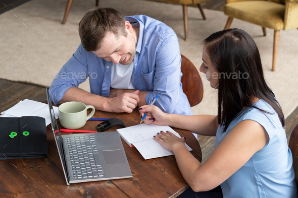 Businesswoman explaining something to her coworker in an office - Stock Photo - Images