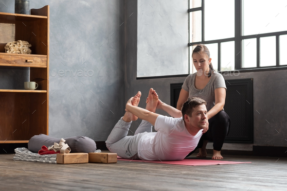 Young caucasian practicing yoga in gym with help of teacher - Stock Photo - Images