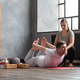 Young caucasian practicing yoga in gym with help of teacher - PhotoDune Item for Sale