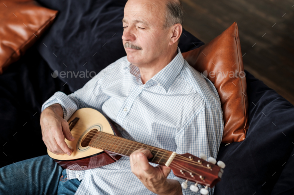 Senior man at home learning to play guitar - Stock Photo - Images