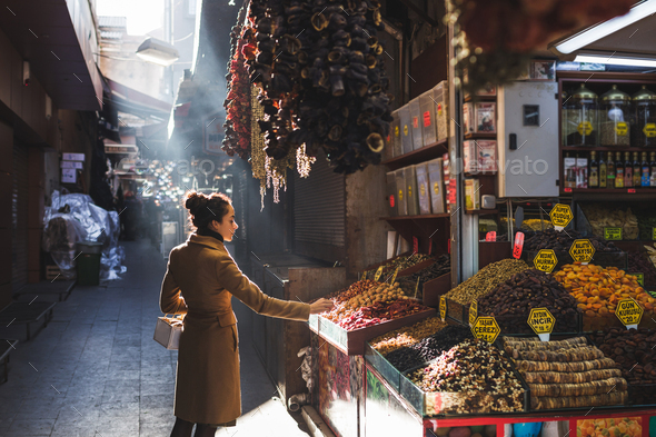 Woman chooses in the market nuts and dried fruit, the buyer tries goods at Grand Bazaar Istanbul - Stock Photo - Images