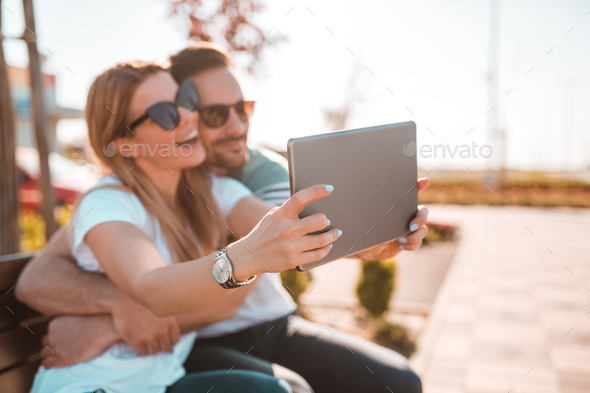 Beautiful young couple with sunglasses taking selfie while they sitting on bench outside - Stock Photo - Images