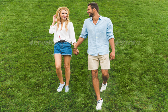 happy couple in love holding hands while walking on green lawn together - Stock Photo - Images