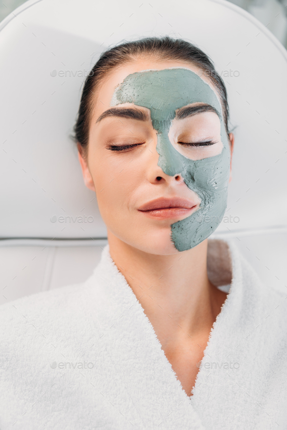 overhead view of beautiful woman with eyes closed and clay mask on face in white bathrobe relaxing - Stock Photo - Images