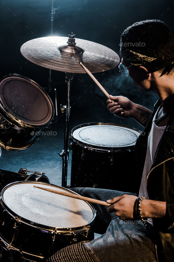 side view mixed race male musician playing drums during rock concert on stage - Stock Photo - Images