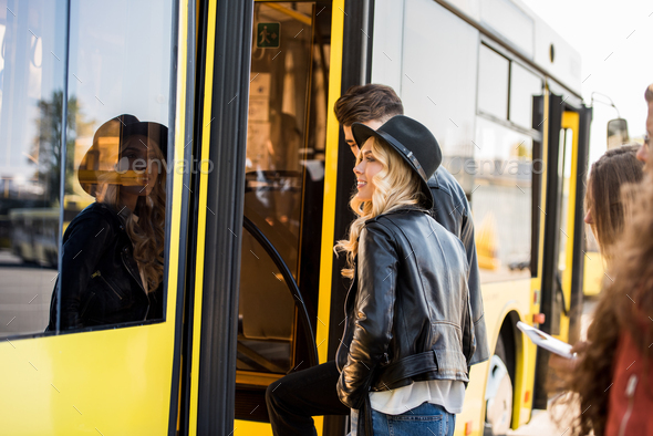 smiling young couple holding hands and entering city bus - Stock Photo - Images