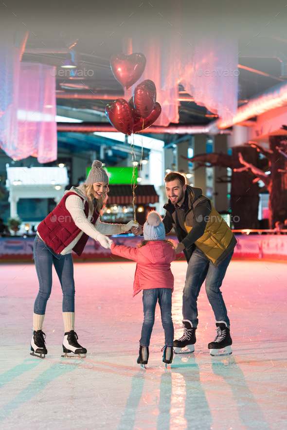 happy family with one child holding heart shaped balloons on skating rink - Stock Photo - Images