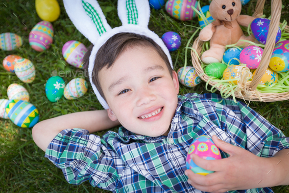 Mixed Race Chinese and Caucasian Boy Outside Wearing Rabbit Ears Playing with Easter Eggs - Stock Photo - Images