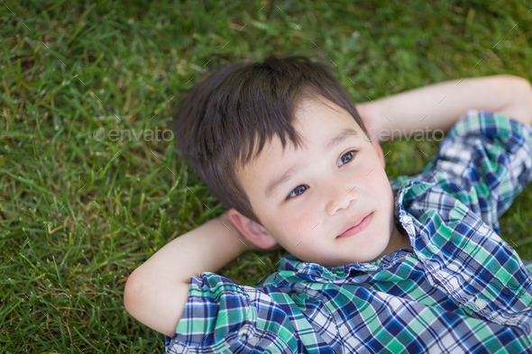 Thoughtful Mixed Race Chinese and Caucasian Young Boy Relaxing On His Back Outside On The Grass - Stock Photo - Images