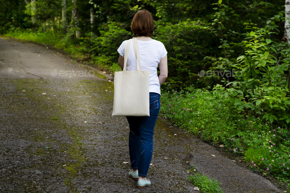 Placeit - Walking woman holding tote bag mockup - Stock Photo - Images