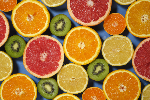 Assortment of various cut raw fruits on blue background, full frame. - Stock Photo - Images