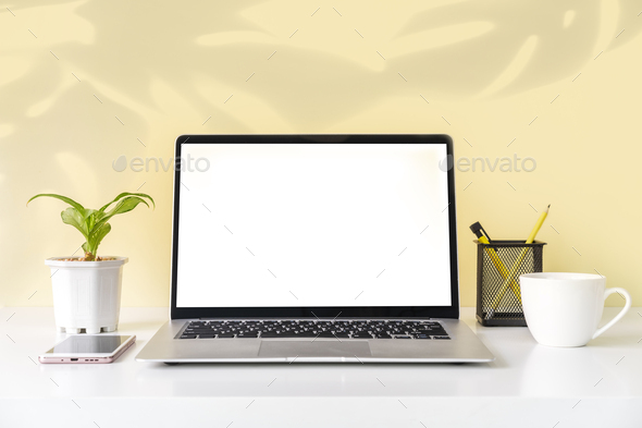 Modern and stylish workspace mock up with blank laptop and desk office supplies