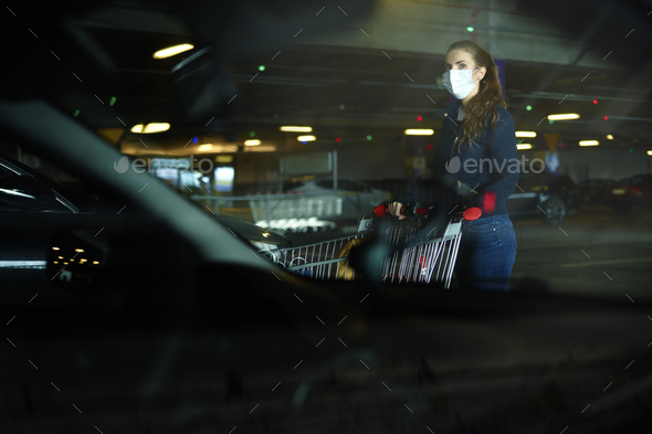 Woman in protective mask with shopping cart in the parking - Stock Photo - Images