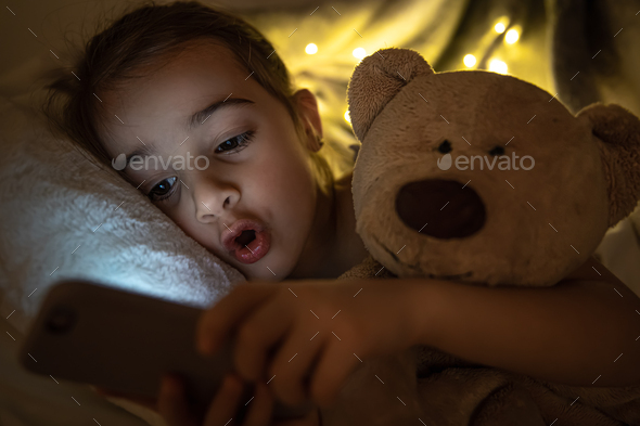 Little girl lies in bed and looks at the smartphone screen at night close up.
