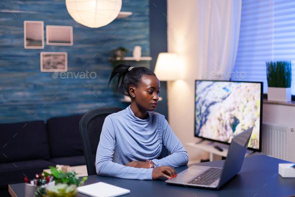 Dark skinned freelancer reading documentation on laptop computer