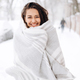 Smiling dark-haired girl wrapped in a gray scarf is standing in a snowy street on a winter day - PhotoDune Item for Sale