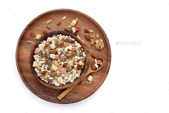 A wooden bowl  Muesli with fruit and nut and a spoon isolated on white background - Stock Photo - Images