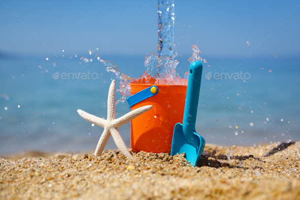 Bright plastic сhildren's beach toys and a starfish on sand near sea. Summer vacation concept - Stock Photo - Images