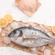 Raw dorada fish or gilt-head bream on ice with lemon and salt over white background - PhotoDune Item for Sale