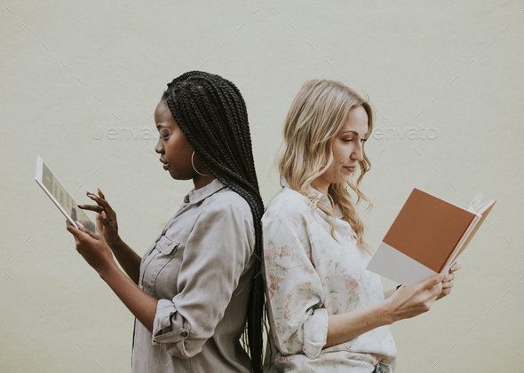 Diverse women reading a book and using a tablet - Stock Photo - Images