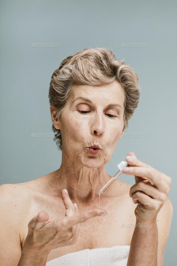 Elderly woman applying moisturizer - Stock Photo - Images