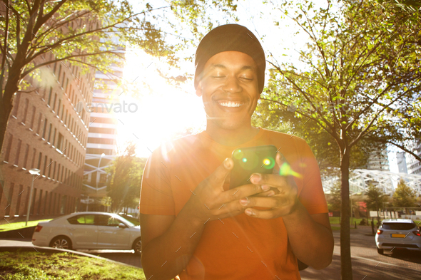 smiling african american man walking in city with mobile phone on sunny day - Stock Photo - Images