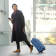 Full length smiling travel man walking at airport with cellphone and luggage - PhotoDune Item for Sale