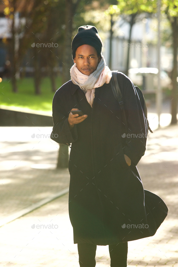 cool african american guy walking in city park with winter jacket beanie and mobile phone - Stock Photo - Images