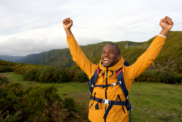 happy african american backpacker standing outdoors with arms raised - Stock Photo - Images