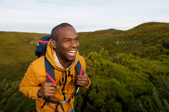 happy african american male backpacker walking in nature - Stock Photo - Images