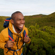 happy african american male backpacker walking in nature - PhotoDune Item for Sale