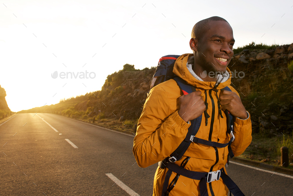 happy young african american male hiker walking on road during sunrise - Stock Photo - Images