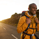 happy young african american male hiker walking on road during sunrise - PhotoDune Item for Sale