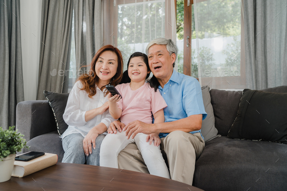 Asian grandparents watch TV with granddaughter at home. - Stock Photo - Images