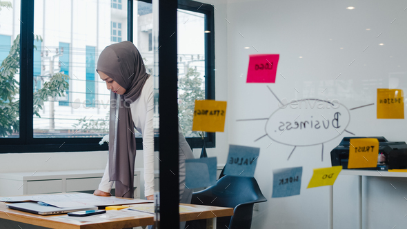 Asia muslim lady drawing work plan think information reminder on paper in new normal office. - Stock Photo - Images
