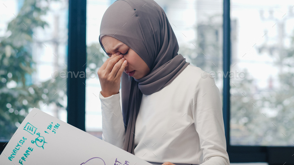 Asia muslim lady drawing work plan think information reminder on paper in new normal office - Stock Photo - Images