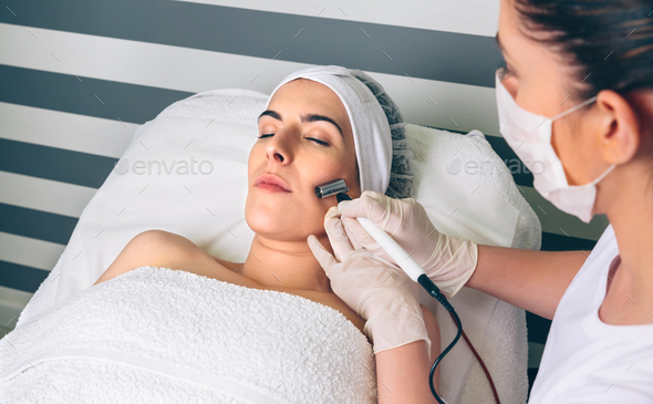 Woman getting rf lifting in her face in clinic - Stock Photo - Images