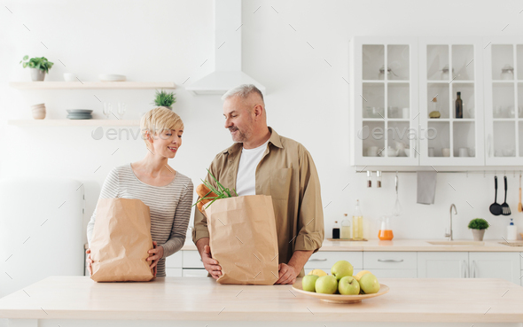 Happy family relationships, couple unpacking fresh products from market in kitchen - Stock Photo - Images