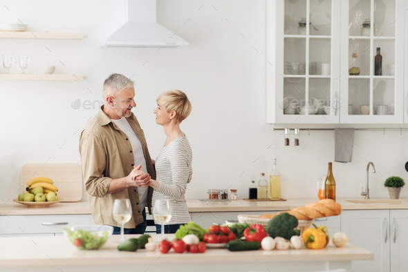 Happy senior couple in love celebrating Valentines day at home together, having romantic dinner - Stock Photo - Images