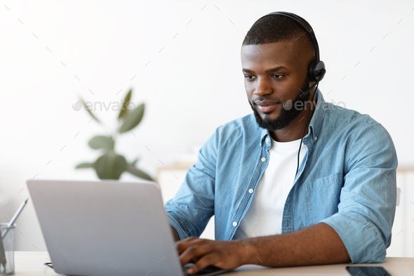Portrait of african american man in headset working on laptop in office - Stock Photo - Images