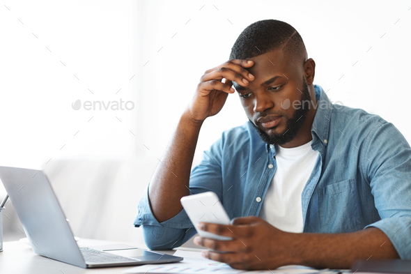 Concerned black freelancer guy looking at smartphone while working at home office - Stock Photo - Images