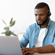 Portrait of african american man in headset working on laptop in office - PhotoDune Item for Sale