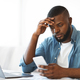 Concerned black freelancer guy looking at smartphone while working at home office - PhotoDune Item for Sale