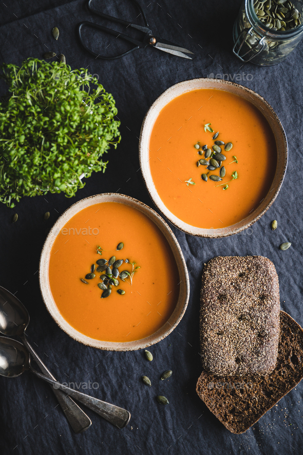 Vegetable creamy healthy soup with pumpkin seeds on a kitchen table. - Stock Photo - Images