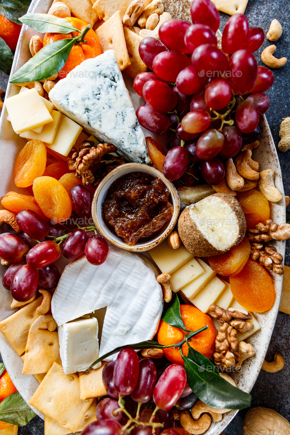 Big cheese board with appetizer assortment. Grape, cheese, nuts, jam and bread. - Stock Photo - Images