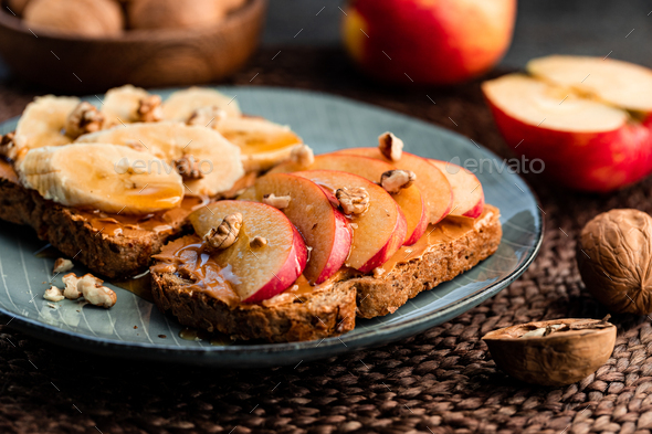 Toasts with peanut butter, apple, banana, walnut and honey. Healthy vegetarian breakfast concept. - Stock Photo - Images
