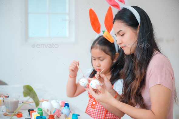 Attractive young woman with little cute girl are preparing for Easter celebration - Stock Photo - Images