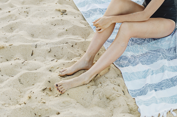 Woman sitting in the sand - Stock Photo - Images