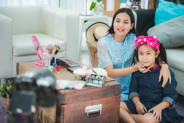 young woman and children girl living at home, work from home to make video online streaming - Stock Photo - Images