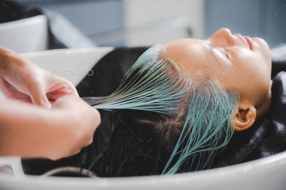 Hairdresser putting mask and coloring on woman's hair in beauty salon - Stock Photo - Images